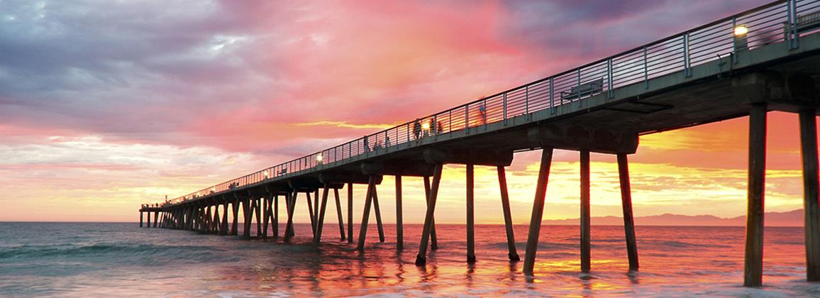 Sun setting behind a boardwalk reaching out into the ocean representing improved performance and achievement