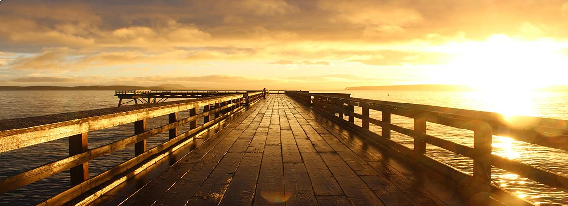 Sun rising over a wooden pier, symbolising a new life direction and a better future