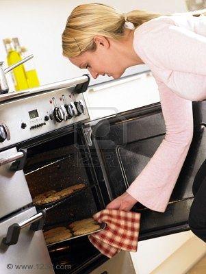 Женщина, вынимающая печенье из духовки