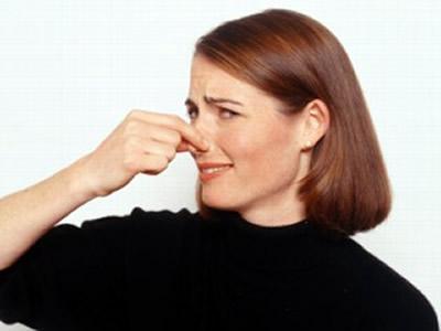 женщина, закрывающая свой нос от неприятного запаха