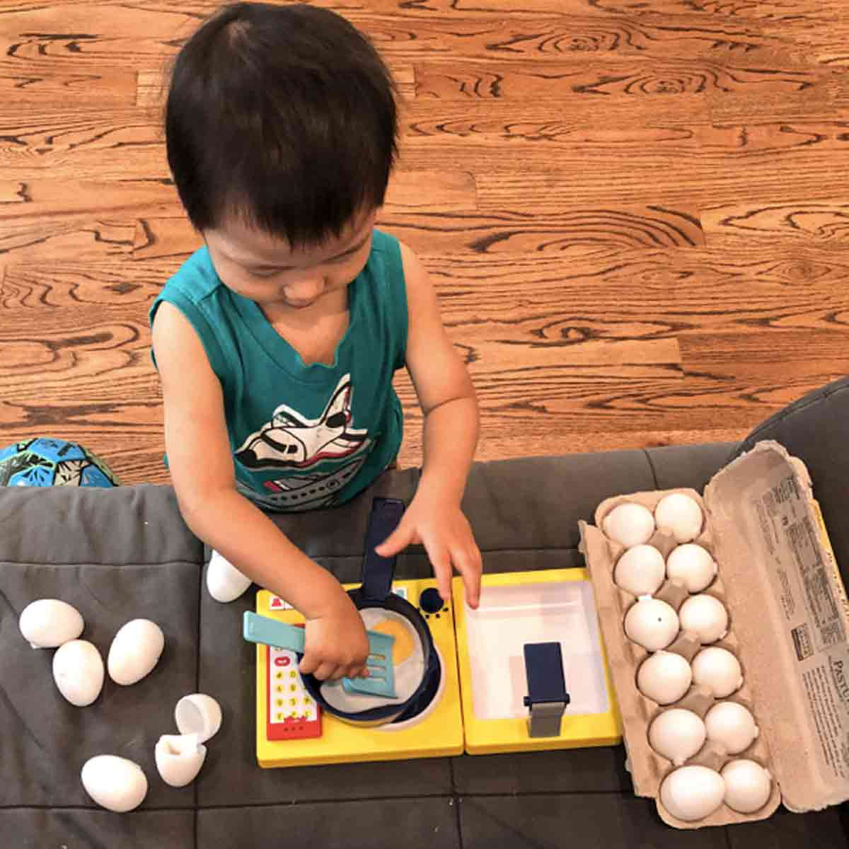 Toddler playing with pretend play felt egg on toy cooking pot