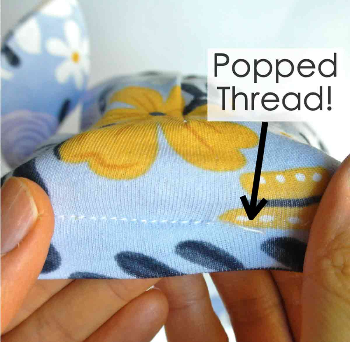 Shows a popped thread on a hem of knit fabric sewn with straight stitch