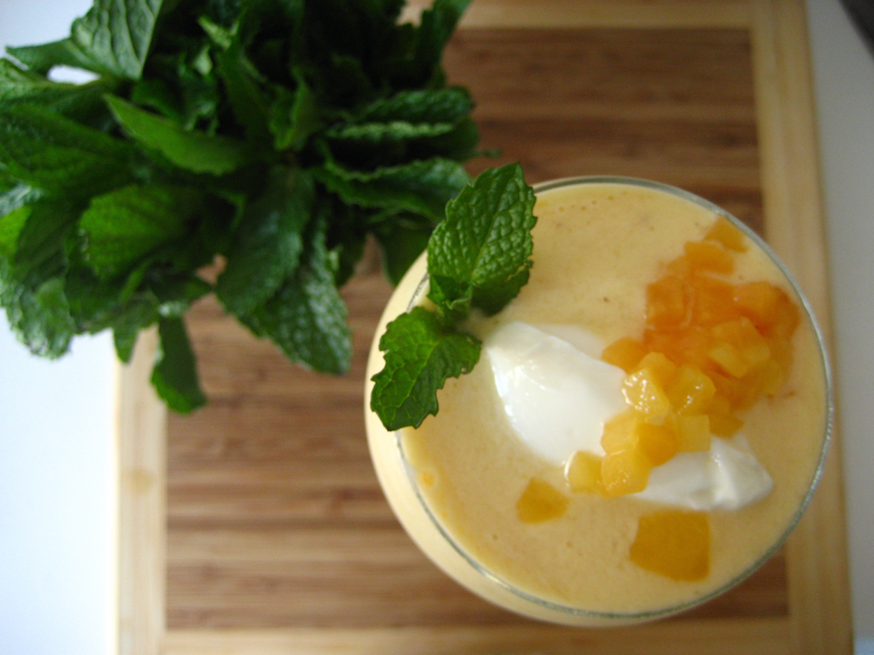 """Normally I just slurp the smoothie out of a plastic quart container, but I decided to """"dress up"""" for company with a dollup of greek yogurt mixed with honey, diced peaches, and a sprig of mint.  By the way, that cutting board is basically the size of my prep space."""
