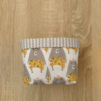 panier de rangement en tissu motif ours gris avec chapeau rose et short jaune moutarde sur fond blanc et intérieur motifs géométriques gris sur fond blanc