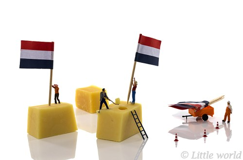 little people putting the dutch red white and blue flags on dutch cheese