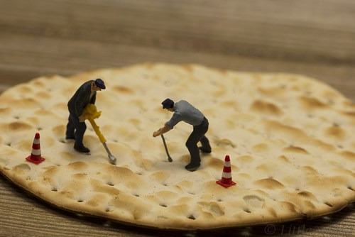 little people making holes in crackers for production