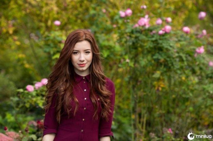mulher de cabelos em campo com flores