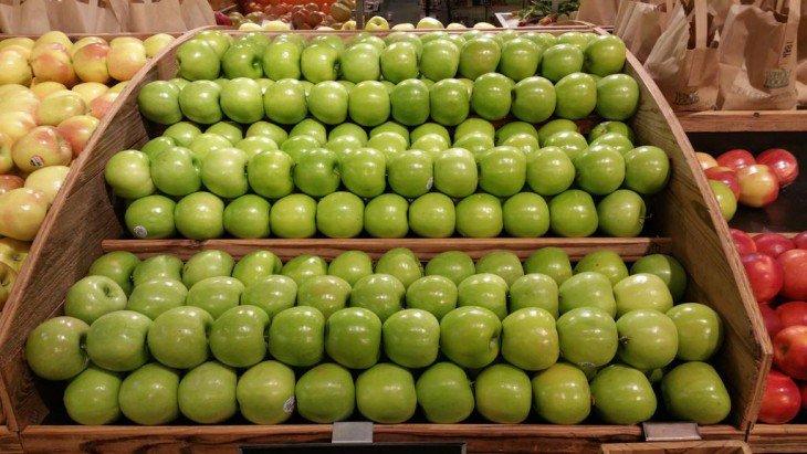 maçãs verdes arranjados em uma prateleira em um shopping