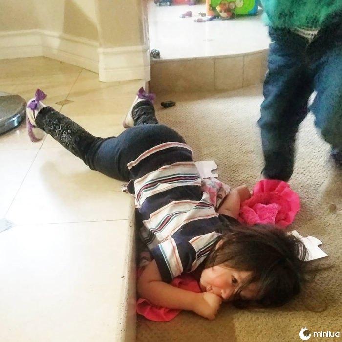 menina na posição rara no chão