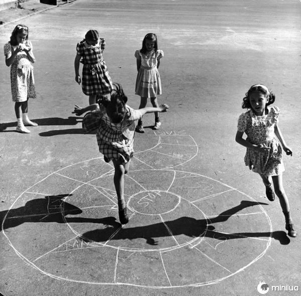 meninas jogando em uma rua em um pequeno avião no chão