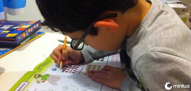 Criança executando exercícios em seu caderno