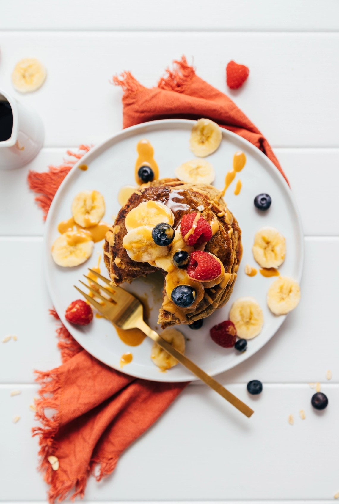 Top down shot of a stack of Peanut Butter Protein Pancakes topped with fresh fruit