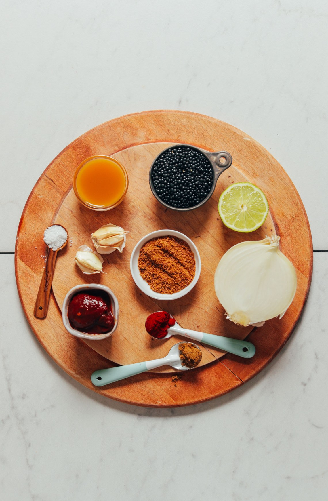 Wood cutting board with ingredients for making Smoky Refried Lentils