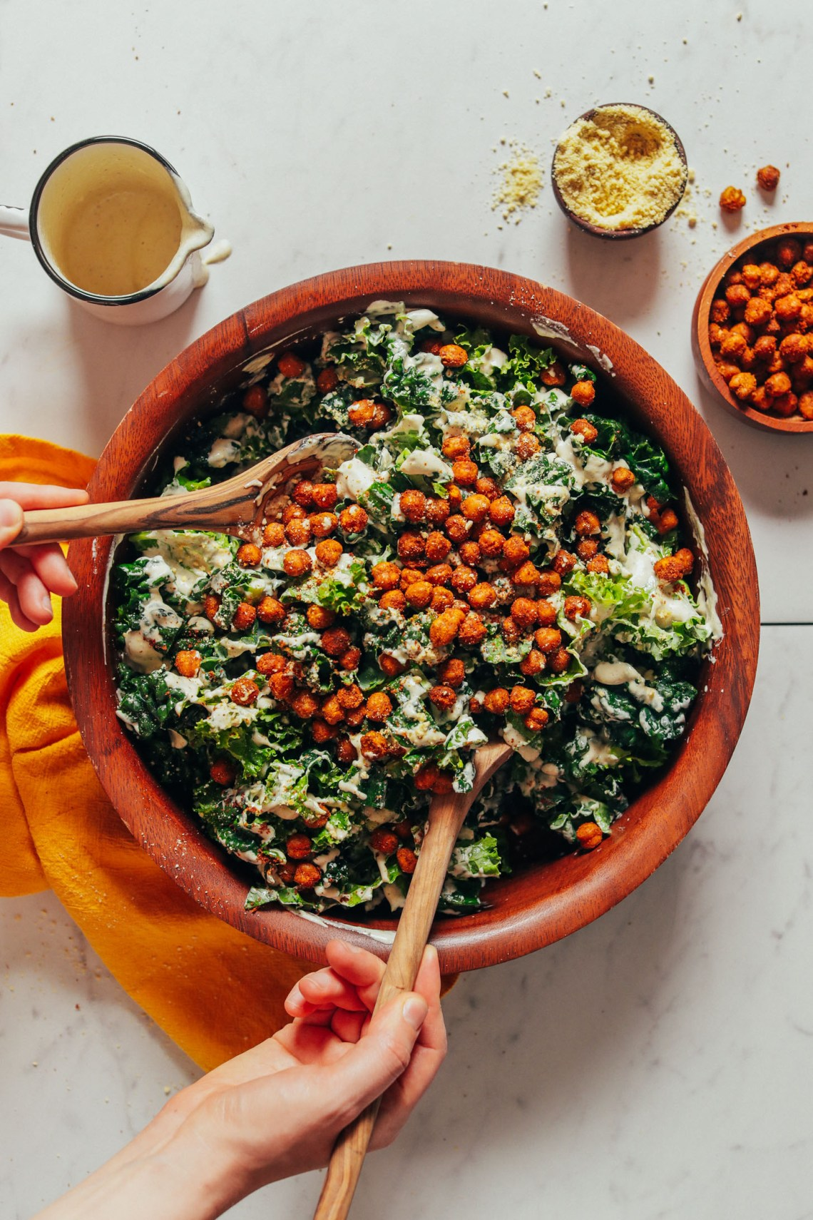 Using wooden salad spoons to toss a bowl of Chickpea Kale Salad topped with tandoori chickpeas
