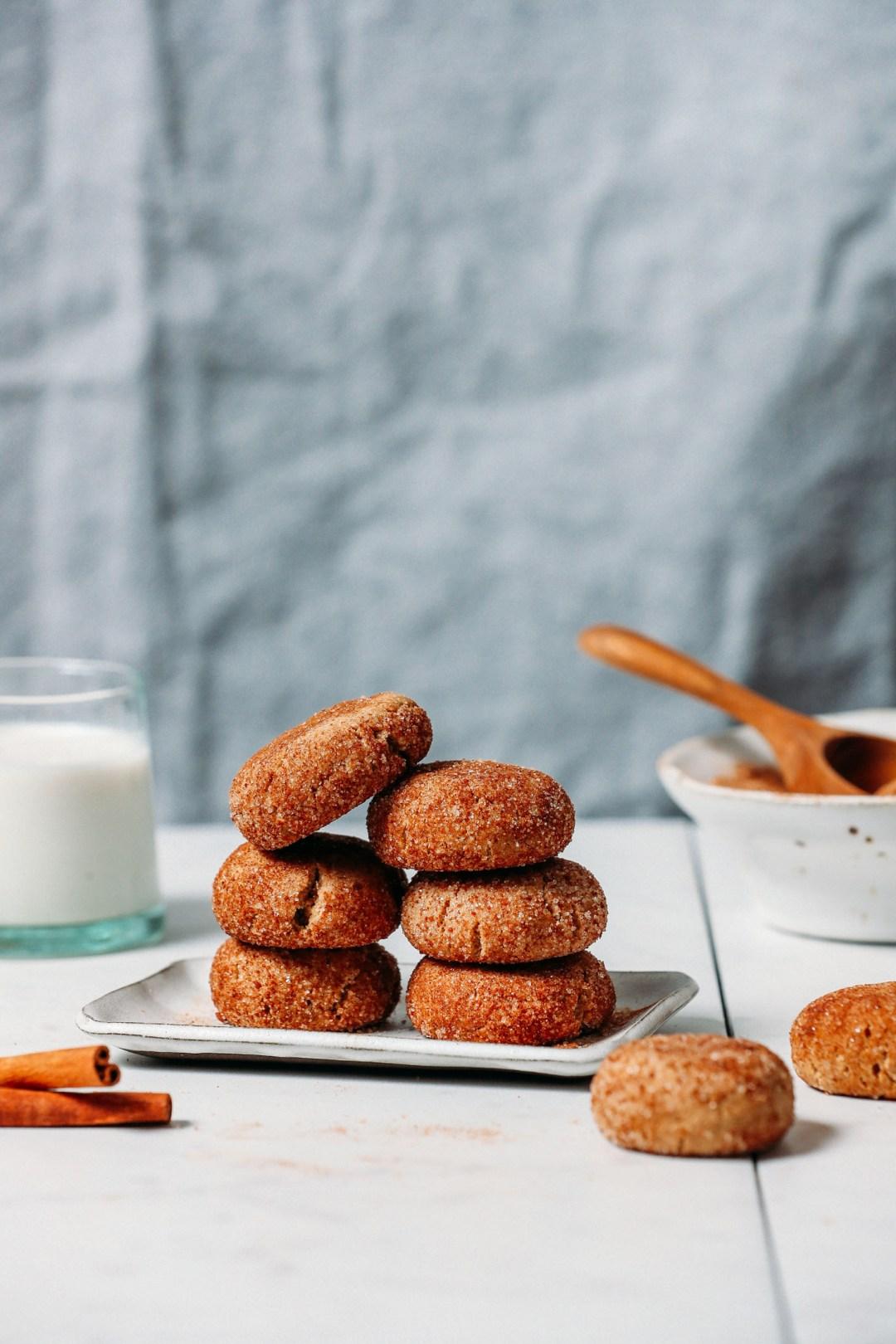 GF Vegan Snickerdoodle Cookies apiladas en un plato junto a un vaso de leche no láctea, una rama de canela y una capa de azúcar de canela
