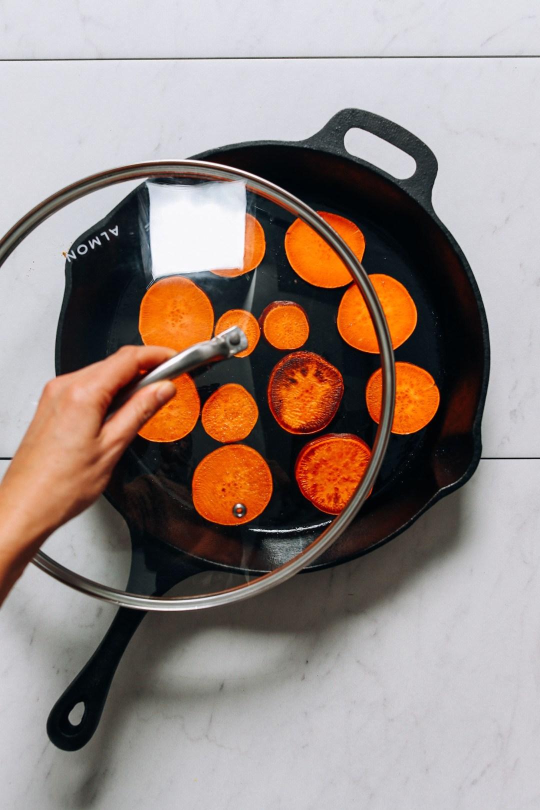 Cubriendo una sartén de batatas para ayudarlos a cocinar completamente