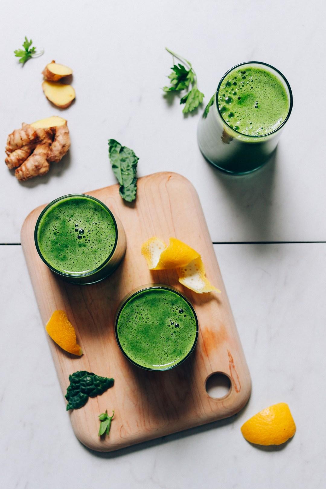 Vasos de jugo verde casero en una tabla de cortar junto a los ingredientes utilizados para hacerlo