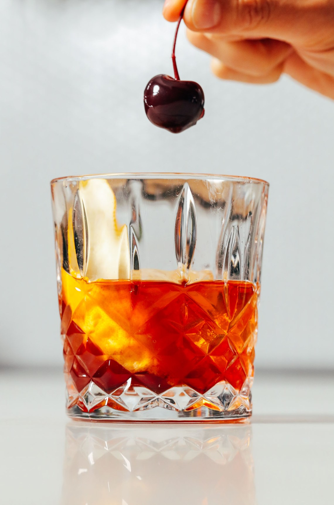 Holding a cocktail cherry over an Old Fashioned