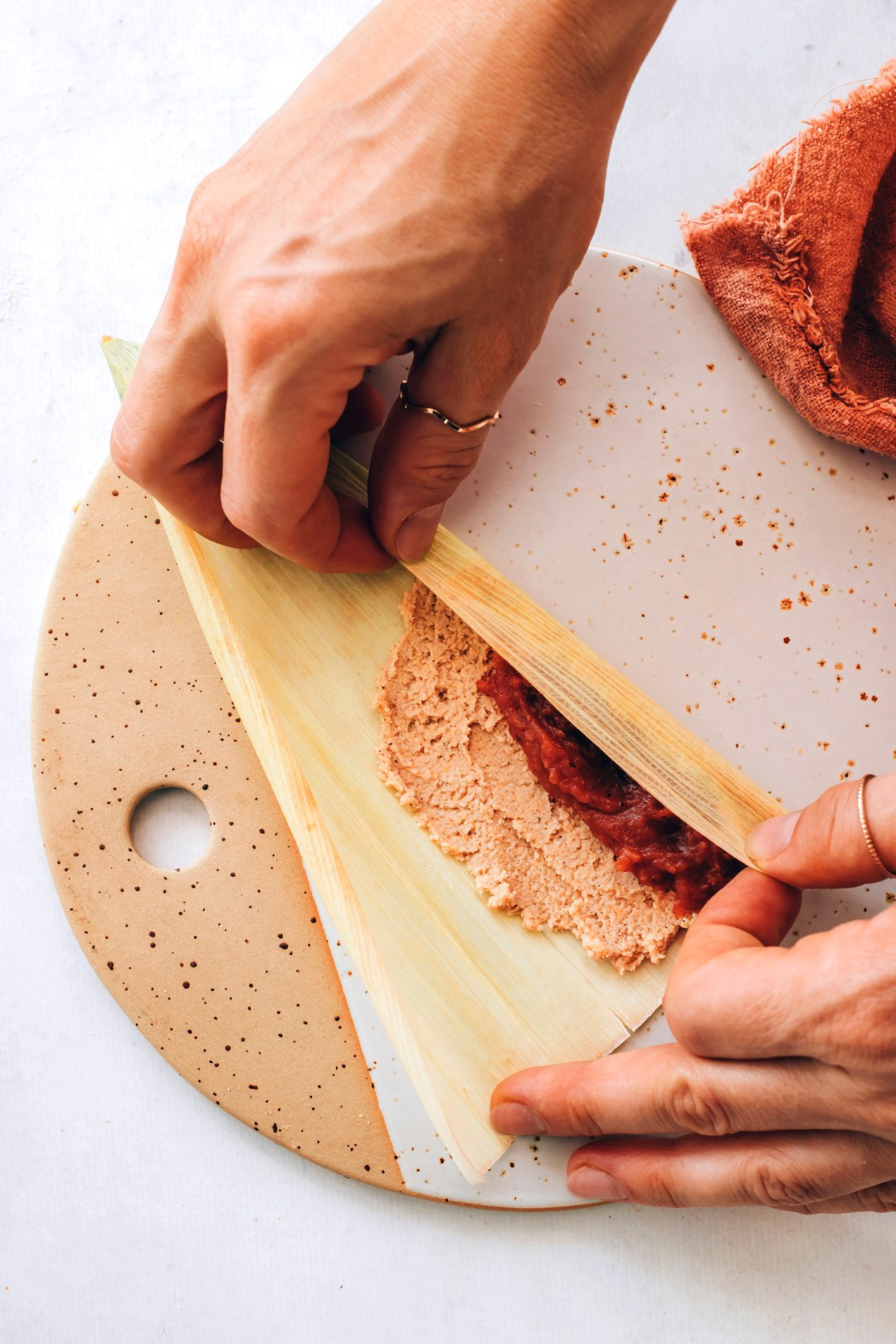 Folding a corn husk over masa filling and apple butter