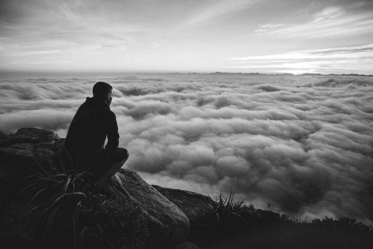 uomo chiede perché su una collina sopra alle nuvole