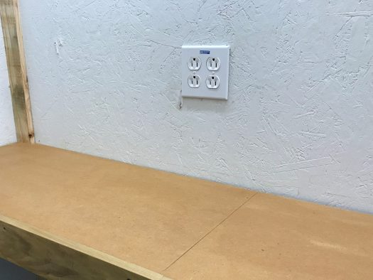 Receptacles installed in wall above workbench
