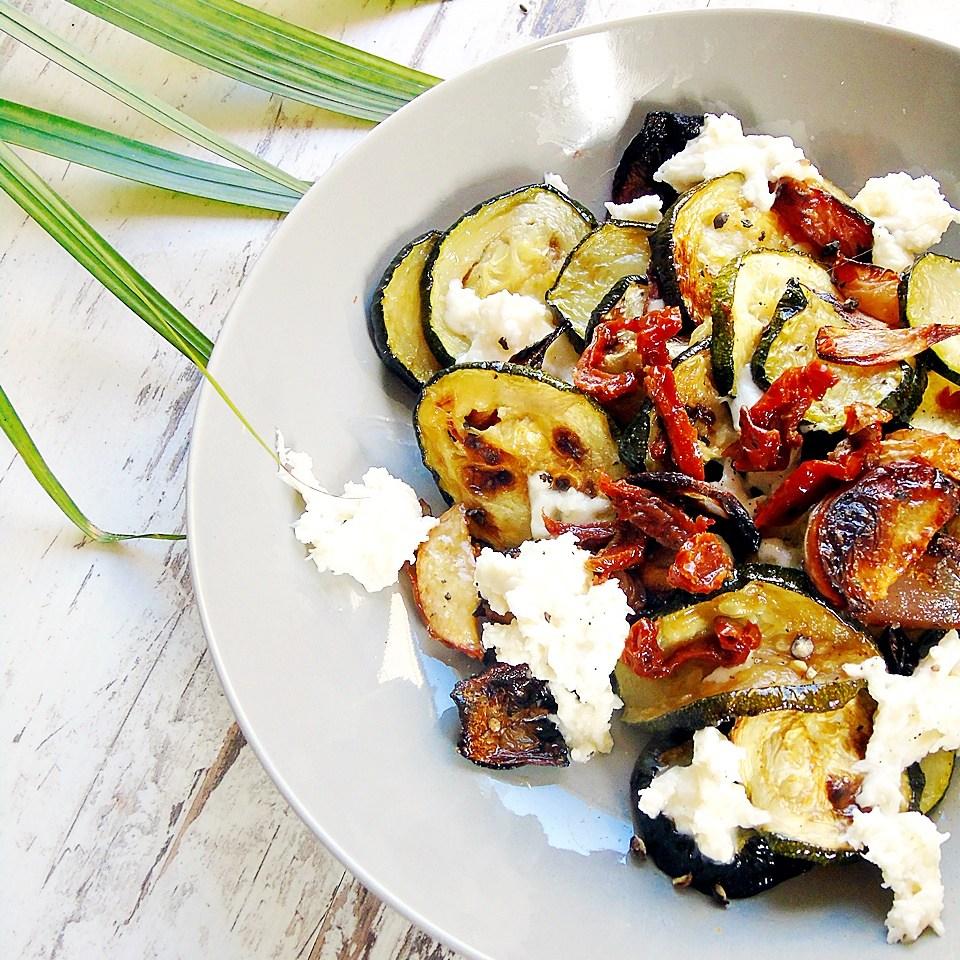 Salat aus gebratenen Zucchini mit Pfirsichen und Mozzarella auf einem grauen Teller