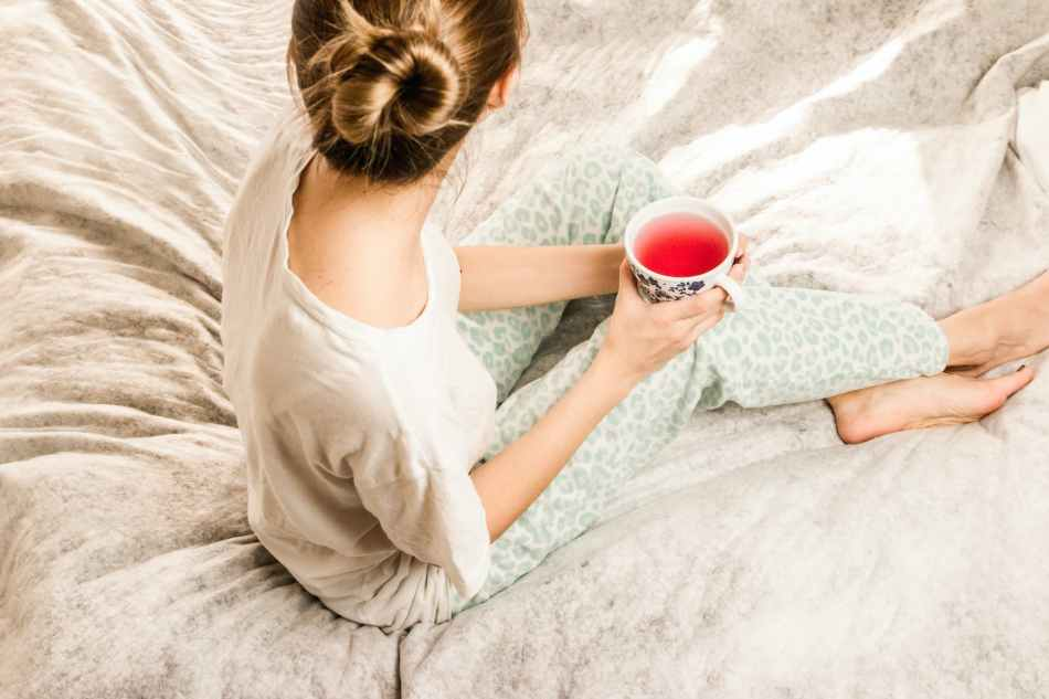 aerial view photography of woman sitting on blanket while holding mug filled with pink liquid looking sideward