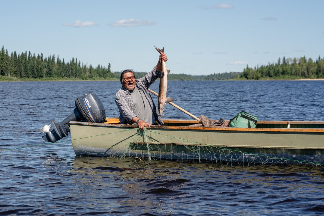A person holds up a fish in a boat on the Attawapiskat River. There is a look of elation on their face.