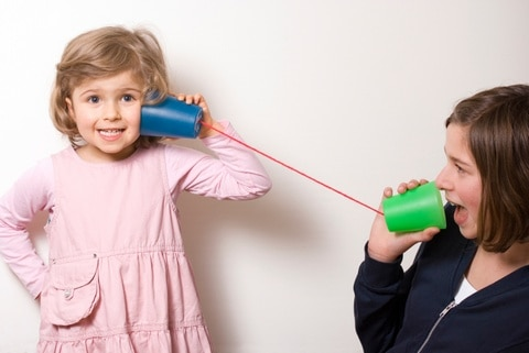 Child listening through a toy string phone.
