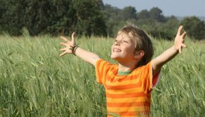 Boy praying in open field