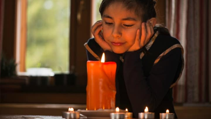 Young teenage girl meditating in candle light