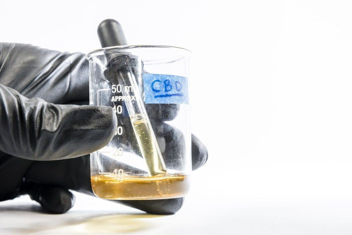 A gloved hand holds a beaker containing amber liquid and a dropper, labeled CBD. Some research suggests CBD could be used as an antibiotic in clinical settings. Cannabinoid antibiotics represent the cutting-edge of research.