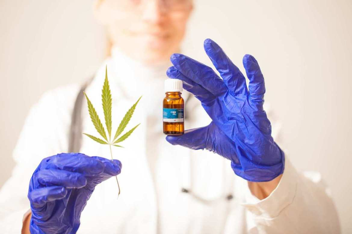 A gloved scientist with a vial of CBD and a hemp leaf. 'Full spectrum' extracts contain more cannabinoids, terpenes, and other beneficial chemicals found in hemp & cannabis. A growing body of scientific research suggests CBD oil can reduce symptoms of inflammation, chronic pain and anxiety, and could even reduce the damage cause by some intestinal diseases.
