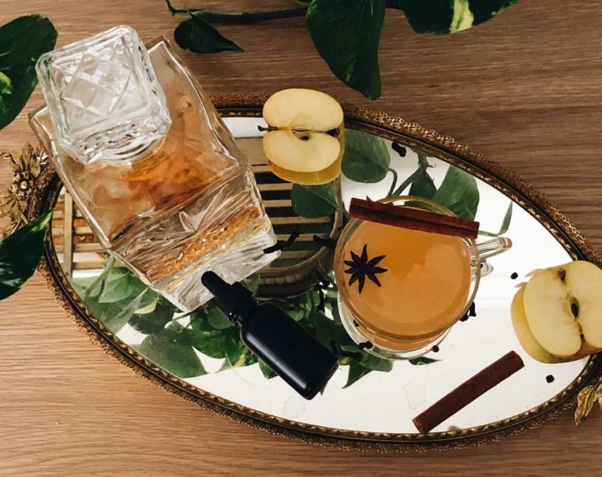 A decanter of bourbon sits on a platter with a bottle of tincture, apples, cloves, and a glass of cider decorated with a cinnamon stick. Chron Vivant's CBD Mulled Apple Cider will warm you up and help relieve the stress of the holidays.
