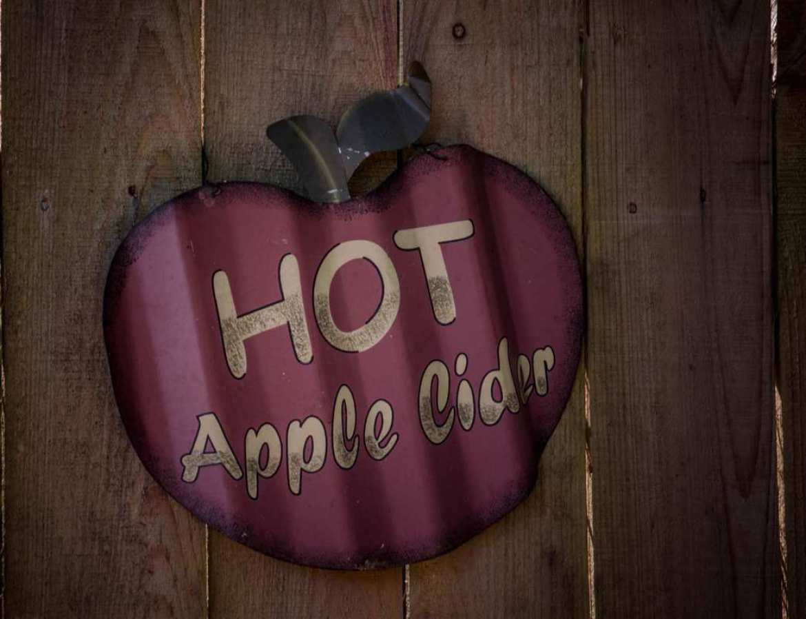 """An antique """"Hot Apple Cider"""" sign, shaped like an apple, painted on a wooden fence. Our hot CBD mulled apple cider will enhance those autumn vibes and help you relax during the busy holiday season."""