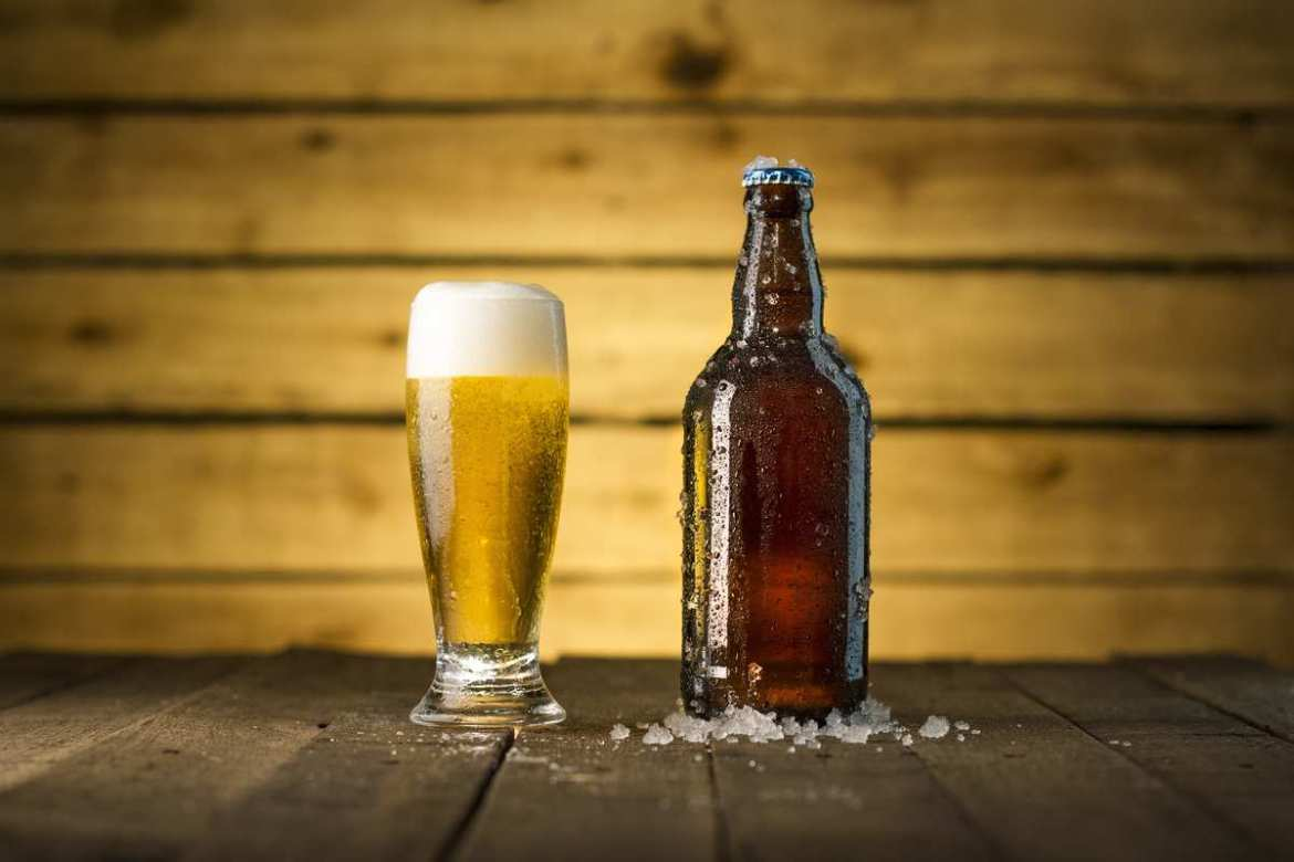 A pale, foamy beer in a glass sits next to a capped brown beer bottle chilling in a small pile of ice. The success of the UK's first CBD beer is likely to lead to more CBD-infused brews in the near future.