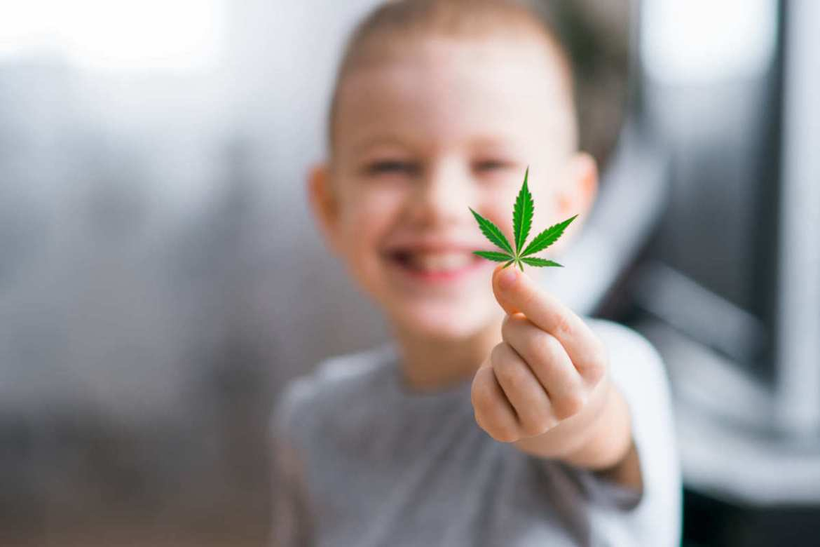 A young child with short hair grins while holding a hemp leaf toward the camera. The British Hemp Association believes that hemp can have a massive positive impact on people in the UK and the planet as a whole, if that government will get out of their way.