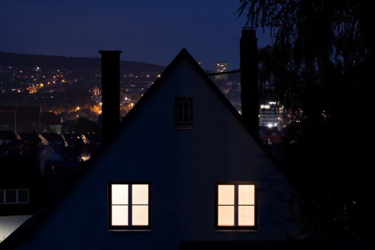 During insomnia, the brain goes into flight-or-fight mode, leaving would-be sleepers too alert to drift off. Photo: A house with its lights on at the top floor, with a night time city in the background.