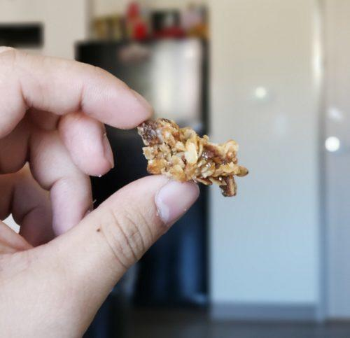 You can eat our hemp granola by the handful, or mix it with milk or yogurt. Photo: A hand holds a chunk of hemp granola.