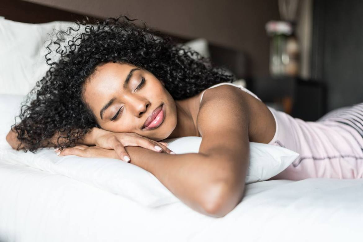 Photo: A woman stretches out in bed enjoying a deep, restful sleep.