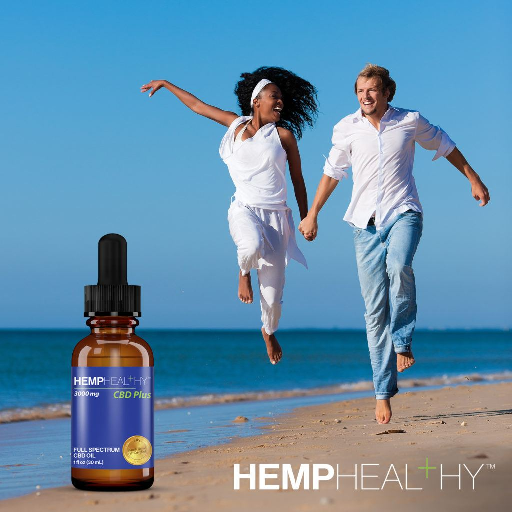 A couple runs on the beach together, dressed in white shirts. A bottle of Hemp Healthy Full Spectrum CBD Oil is shown.