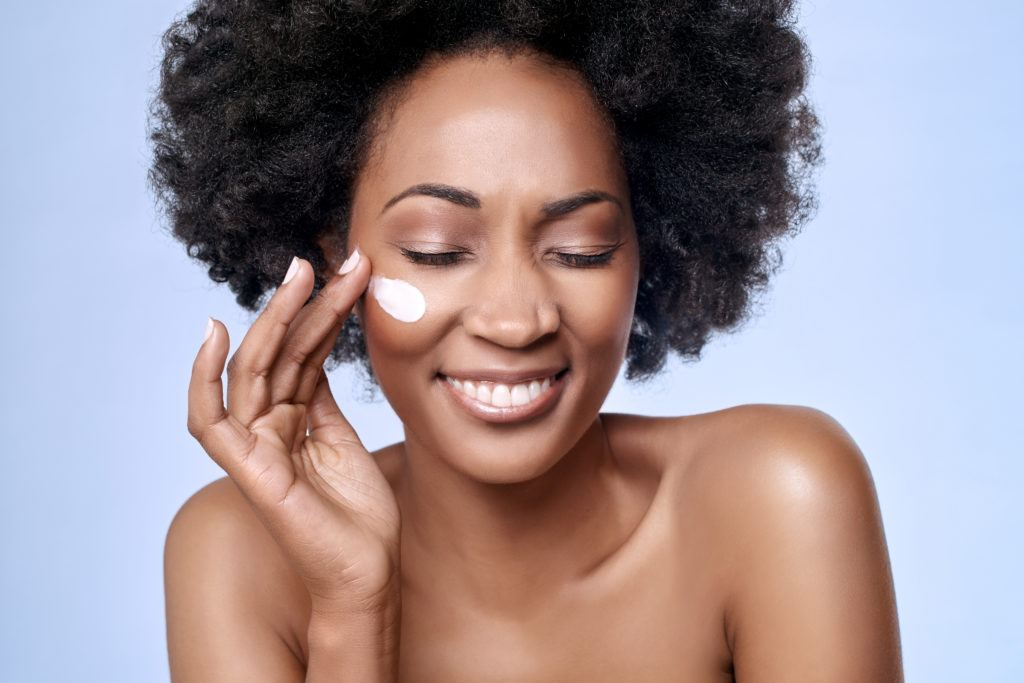 Ministry of Hemp selected the best CBD skin care and hemp beauty products out of dozens on the market. Photo: A black woman with natural hair smiles as she applies a skin care product to her cheek.