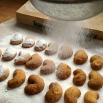 sieving icing sugar onto the kourabiedes