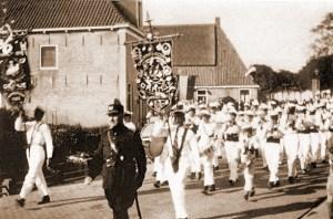 Veldwachter De Jong tijdens rondgang door het dorp met muziekkorps Oranje