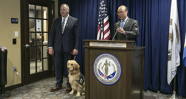 """Ramsey County Attorney John Choi introduces Norie, a laid back but highly trained golden retriever, as his office's new """"facility animal."""" The dog will help victims and witnesses stay at ease through the difficult prosecution process. The animal's handler, victim/witness advocate Bill Kubes, is pictured at left. (Staff photo: Kevin Featherly)"""