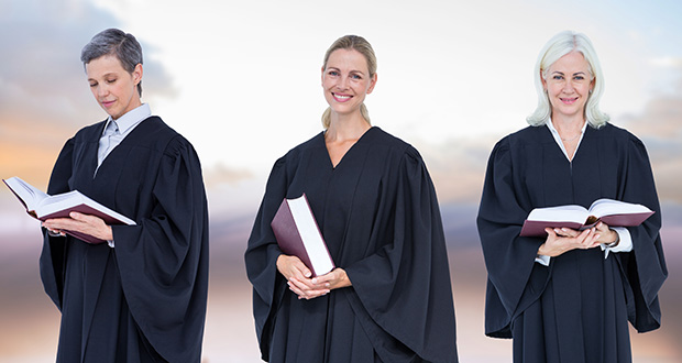 Women Judges holding books in front of sky clouds