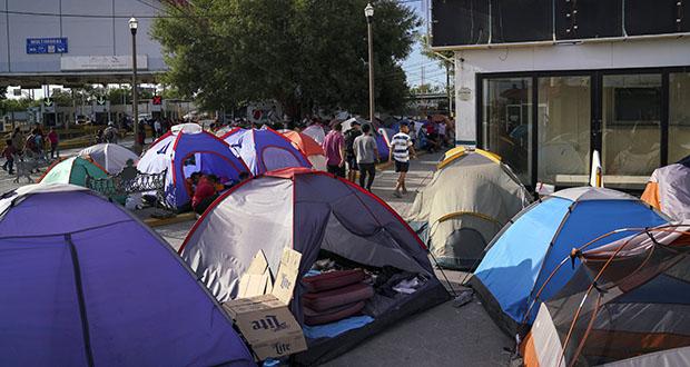 In this Aug. 30 photo, asylum seekers walk by an encampment near the Gateway International Bridge in Matamoros, Mexico. (AP file photo)