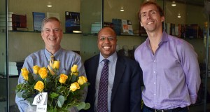 U of M Law School Professor Brad Clary, left, received a surprise bouquet of yellow roses to notify him that he was awarded the Thomas F. Blackwell Memorial Award for outstanding achievement in the field of legal writing. He is joined by Dean Garry Jenkins and Professor Christopher Soper, left.
