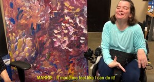 "Plaintiff Marrie Bottelson, an artist who lives with cerebral palsy, wanted in 2013 to integrate deeper into the community. In September 2018 — after the court certified the case as a class action — Bottelson's request was finally granted. In this screen grab from a YouTube video, Bottelson displays her painting, ""Feathers,"" which she says resulted from an artistic exploration of the way her cerebral palsy naturally causes her brush to move across the canvas. (Parternship Resources Inc. via YouTube)"