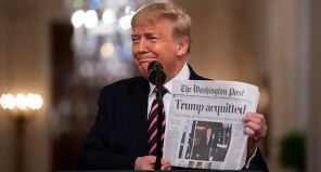"""President Donald Trump holds up a newspaper with a headline that reads """"Trump acquitted"""" as he speaks in the East Room of the White House on Feb. 6. (AP photo)"""